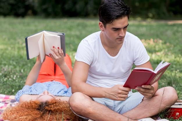 De jonge het houden van boeken van de paarlezing in openlucht