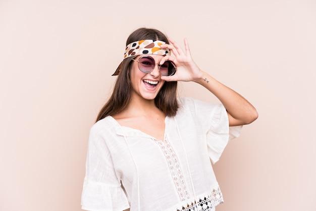 De jonge hipster kaukasische vrouw isoleerde opgewekt het houden van ok gebaar op oog.