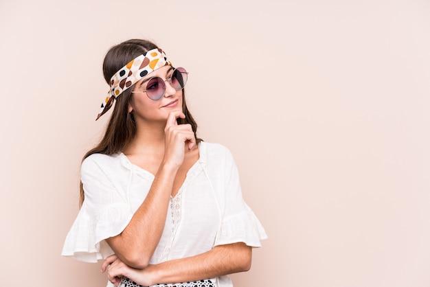 De jonge hipter kaukasische vrouw isoleerde zijdelings het kijken met twijfelachtige en sceptische uitdrukking.