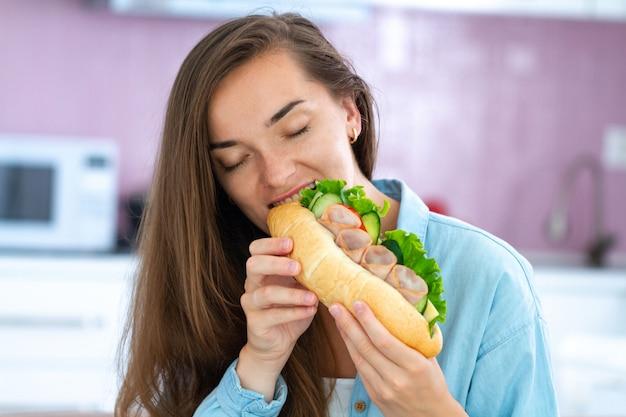 De jonge hongerige vrouw eet sandwich en geniet van voedsel. voedselverslaving.