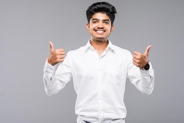 De jonge indische mens die zich over geïsoleerde grijze muur bevinden die goed doend positief gebaar met hand goedkeuren, beduimelt omhoog glimlachend en gelukkig voor succes