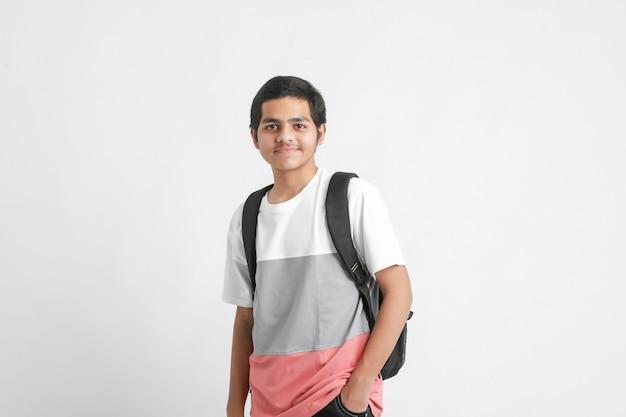 De jonge indische schooltas van de studentholding op witte muur