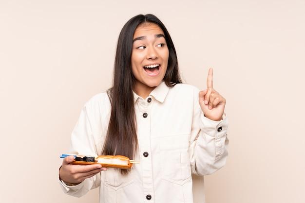 De jonge indische sushi van de vrouwenholding op beige muur die de oplossing willen realiseren terwijl het opheffen van een vinger