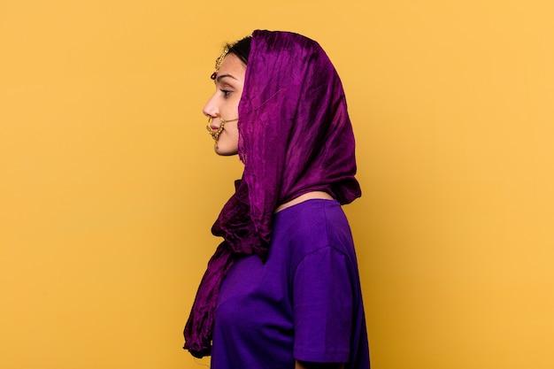 De jonge indische vrouw die traditionele sari-kleren draagt die op gele muur worden geïsoleerd die links, zijwaarts staart stelt