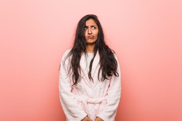 De jonge indische vrouw die verwarde pyjama draagt, voelt twijfelachtig en onzeker
