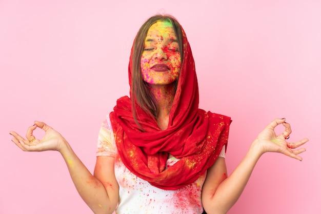 De jonge indische vrouw met kleurrijk holipoeder op haar gezicht op roze muur in zen stelt