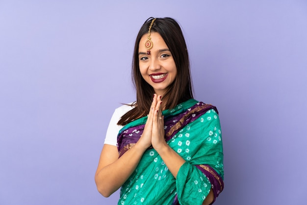 De jonge indische vrouw op purpere muur houdt palm samen.