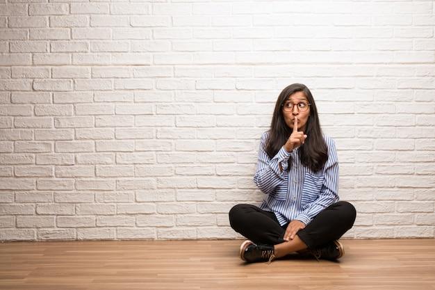 De jonge indische vrouw zit tegen een bakstenen muur die een geheim houdt of om stilte vraagt.