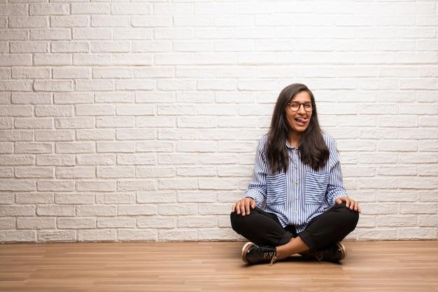 De jonge indische vrouw zit tegen een bakstenen muuruitdrukking van vertrouwen en emotie, pret en vriendschappelijk