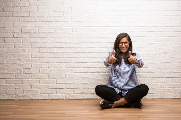 De jonge indische vrouw zit tegen een vrolijke en opgewekte bakstenen muur, glimlachend en opheffend haar