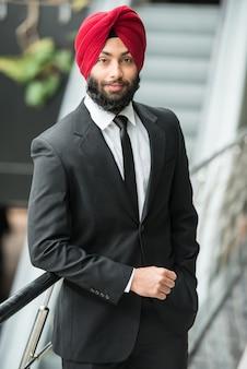 De jonge indische zakenman in tulband stelt