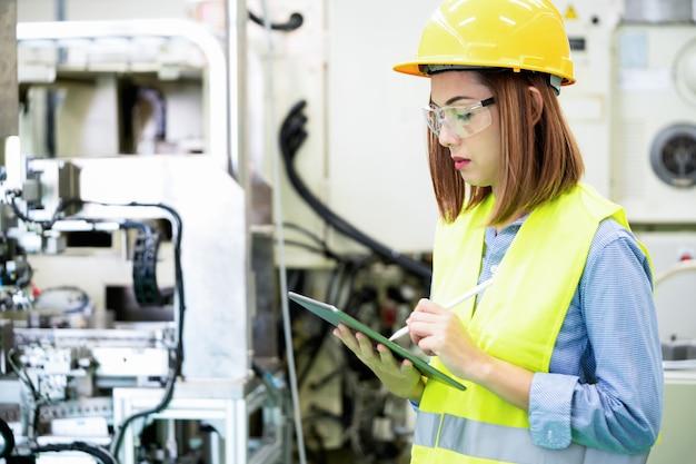 De jonge ingenieursvrouw controleert de machine en het materiaal in de automatiseringsfabriek.