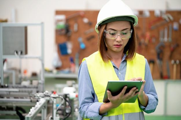 De jonge ingenieursvrouw controleert programmering in de automatiseringsfabriek.