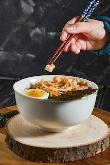 De jonge japanse vrouw die aan het eten is, smaakt heerlijke udon ramen - japanse ramen-soep met kip