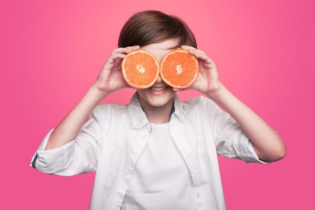 De jonge jongen bedekt zijn ogen met een gesneden sinaasappel die bij camera op een roze muur glimlacht