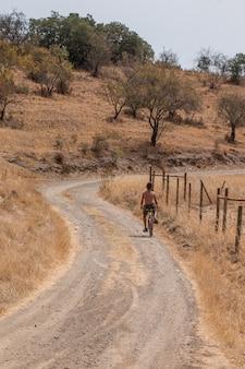 De jonge jongen berijdt een fiets op een landweg