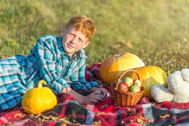 De jonge jongen die van de roodharige op een picknickdeken rust