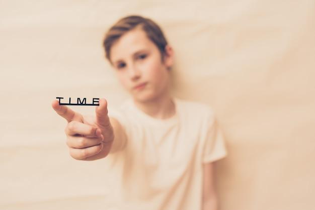 De jonge jongen houdt het woordtijd in zijn hand. selectieve aandacht
