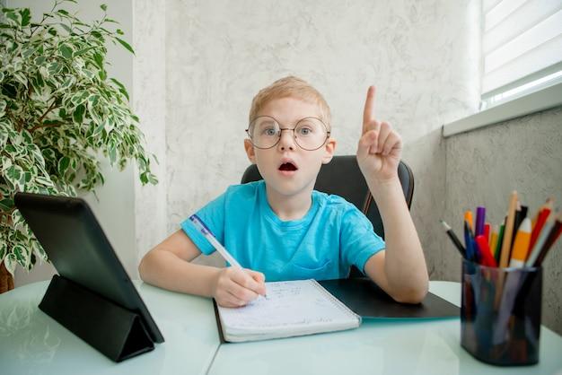 De jonge jongen leert thuis door tablet. afstandsonderwijs in quarantaine.