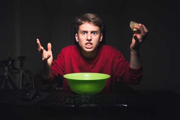 De jonge jongen met de spaanders in zijn hand bekijkt met een verontwaardiging het computerscherm