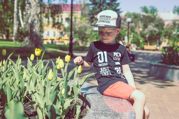 De jonge jongen ruikt tulpenbloem in de lentetuin