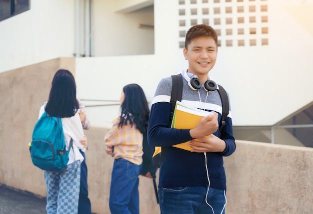 De jonge jongen van de studententiener of middelbare schoolstudent dragende notitieboekjes van de schooltasholding met vrienden op achtergrond