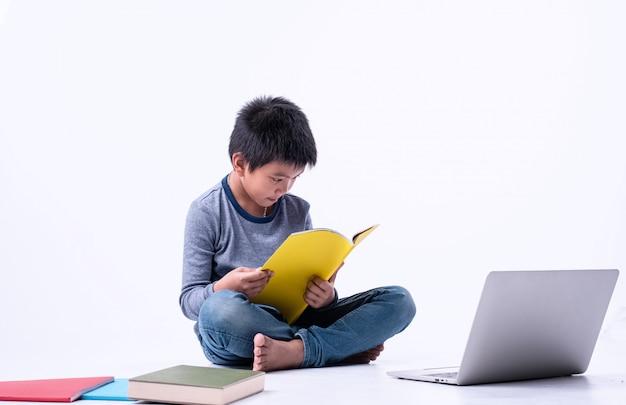 De jonge jongenszitting op het boek van de benedenverdiepingslezing met geinteresseerd gevoel