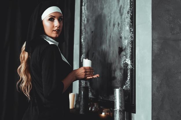 De jonge katholieke non houdt kaars in haar handen. foto op zwarte achtergrond. zijaanzicht.