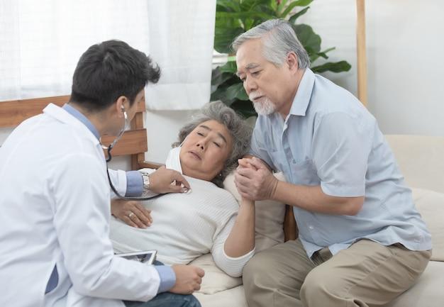 De jonge kaukasische arts luistert hartslag door gebruikend stethoscoop met hogere oude aziatische vrouwelijke patiënt over ziektesymptoom