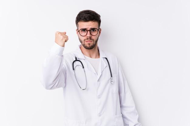 De jonge kaukasische artsenmens isoleerde tonend vuist aan camera, agressieve gelaatsuitdrukking.