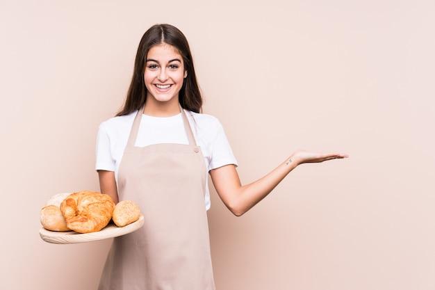De jonge kaukasische bakkersvrouw isoleerde het tonen van een exemplaarruimte op een palm en het houden van een andere hand op taille.