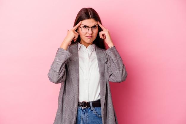 De jonge kaukasische bedrijfsvrouw die op roze muur wordt geïsoleerd, concentreerde zich op een taak, met wijsvingers die het hoofd richten.