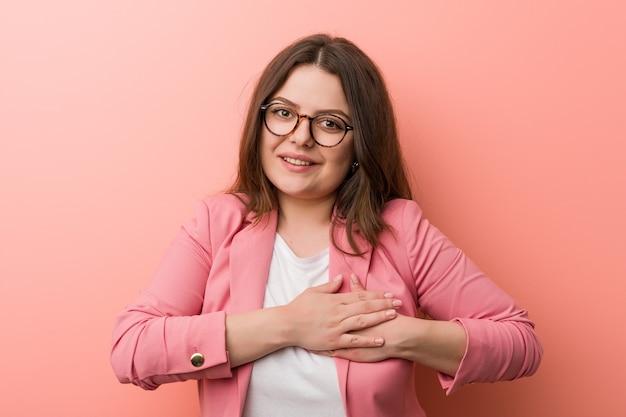 De jonge kaukasische bedrijfsvrouw heeft een vriendelijke uitdrukking en drukt de handpalm tegen de borst. liefde concept.