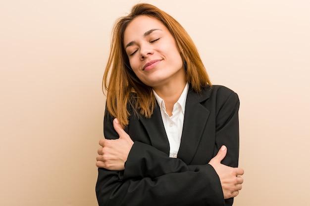 De jonge kaukasische bedrijfsvrouw omhelst zich, onbezorgd en gelukkig lacht.
