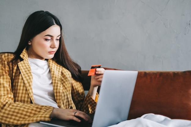 De jonge kaukasische creditcard van de vrouwenholding, die laptop computer gebruikt en online winkelt