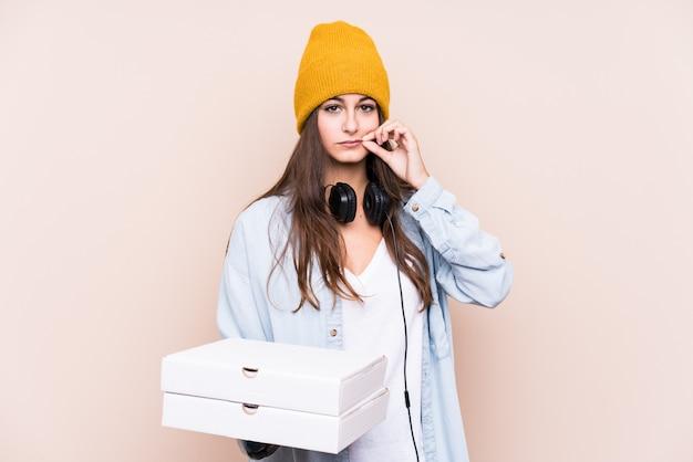 De jonge kaukasische die pizza's van de vrouwenholding met vingers op lippen worden geïsoleerd die een geheim houden.