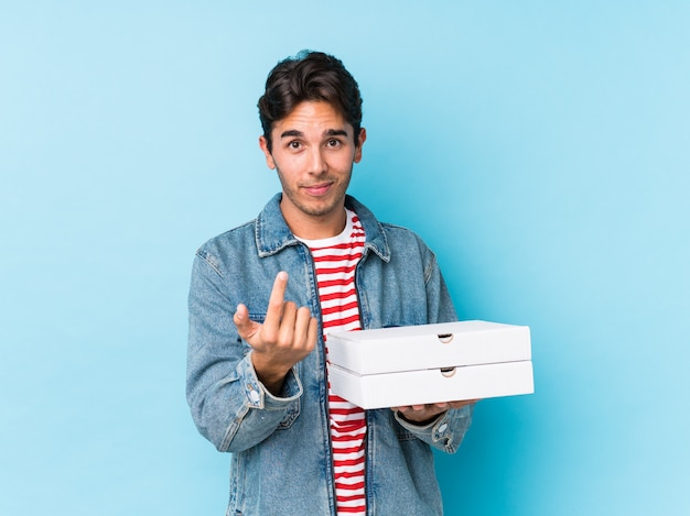 De jonge kaukasische geïsoleerde pizza's van de mensenholding richtend met vinger op u alsof uitnodigend dichterbij kom.