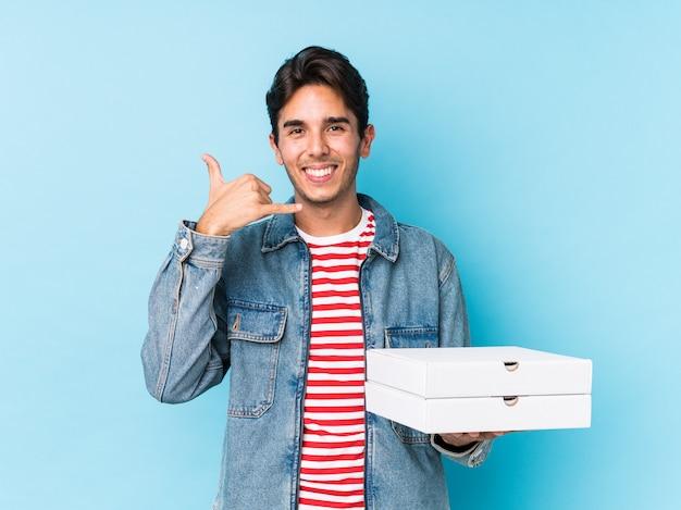 De jonge kaukasische geïsoleerde pizza's van de mensenholding tonend een mobiel telefoongesprekgebaar met vingers.