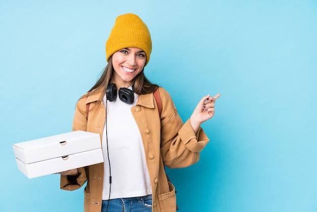 De jonge kaukasische geïsoleerde pizza's van de vrouwenholding glimlachen en wijzen opzij, die iets op lege ruimte tonen.
