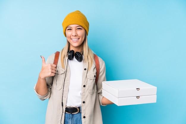 De jonge kaukasische geïsoleerde pizza's van de vrouwenholding glimlachend en duim opheffen