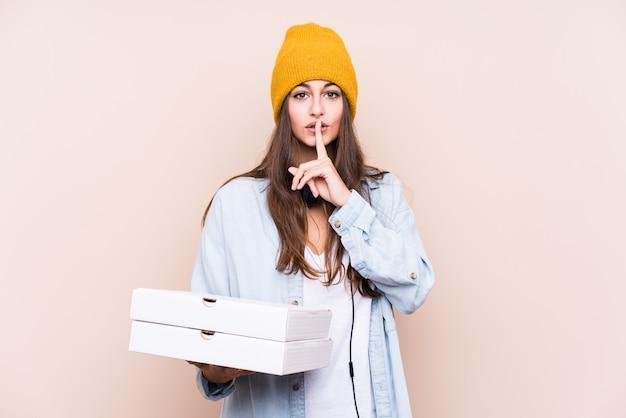 De jonge kaukasische geïsoleerde pizza's van de vrouwenholding het houden van een geheim of het vragen om stilte.