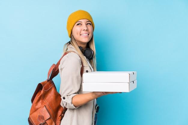 De jonge kaukasische geïsoleerde pizza's van de vrouwenholding kijkt opzij glimlachend, vrolijk en aangenaam.