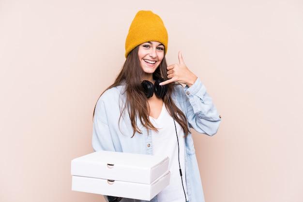 De jonge kaukasische geïsoleerde pizza's van de vrouwenholding tonend een mobiel telefoongesprekgebaar met vingers.