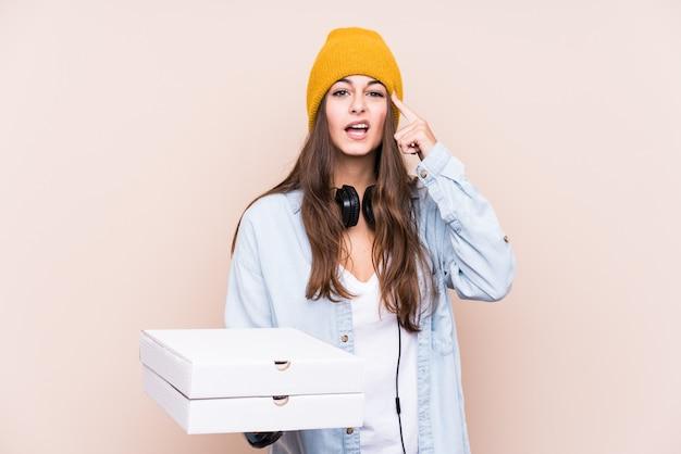 De jonge kaukasische geïsoleerde pizza's van de vrouwenholding tonend een teleurstellingsgebaar met wijsvinger.