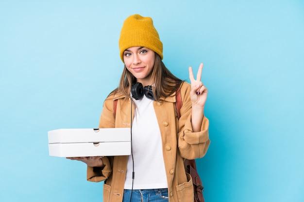 De jonge kaukasische geïsoleerde pizza's van de vrouwenholding tonend nummer twee met vingers.