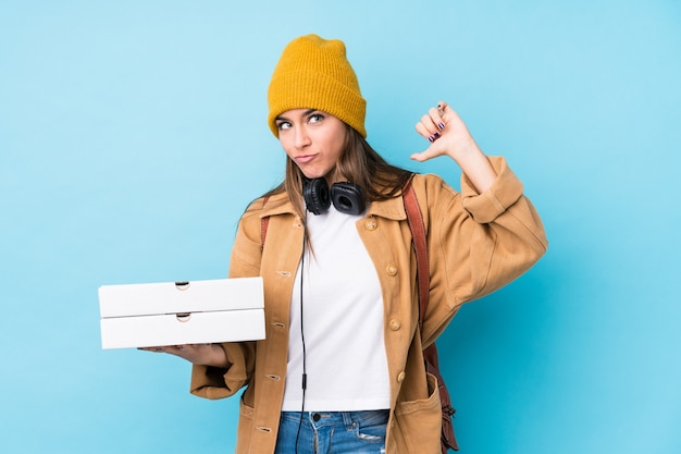De jonge kaukasische geïsoleerde pizza's van de vrouwenholding voelt trots en zelfverzekerd, te volgen voorbeeld.