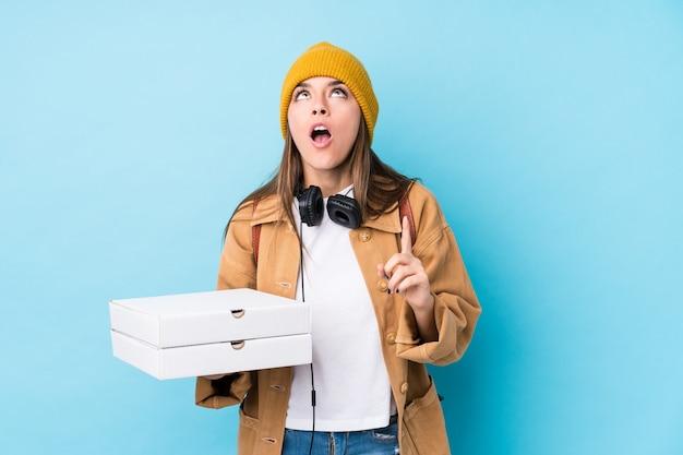 De jonge kaukasische geïsoleerde pizza's van de vrouwenholding wijzend bovenkant met geopende mond.