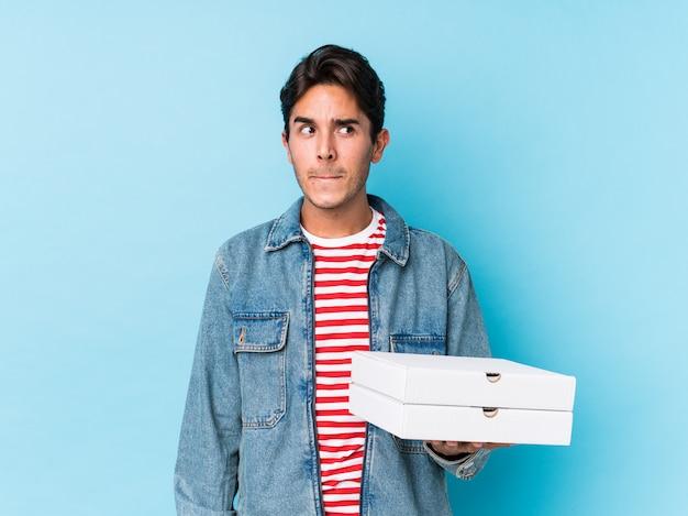De jonge kaukasische geïsoleerde pizza van de mensenholding verward, voelt twijfelachtig en onzeker.