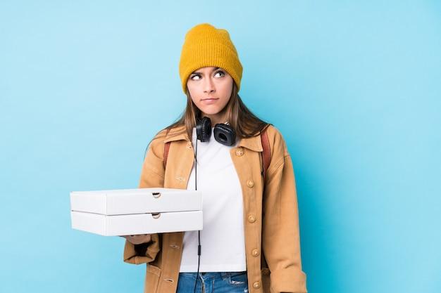 De jonge kaukasische geïsoleerde pizza van de vrouwenholding verward, voelt twijfelachtig en onzeker.