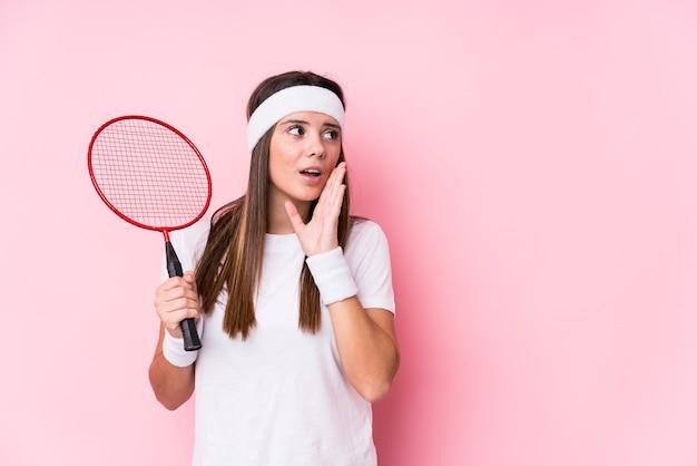De jonge kaukasische geïsoleerde vrouw die badminton speelt zegt een geheim heet het remmen nieuws en kijkt opzij